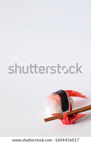Shrimp sushi with seaweed wrap on rice with blurred chopsticks on red origami crane chopstick rest in foreground isolated on white background.  Vertical image. Food and dining in Japan concept. #1604456017