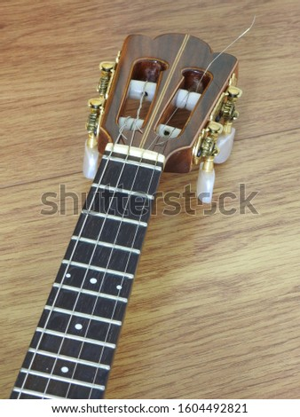 Partial view of the arm of a cavaquinho (Brazilian stringed musical instrument) that has 4 strings, on a wooden surface. #1604492821