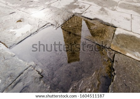 View of Giotto's bell tower in Florence reflected in a puddle #1604511187