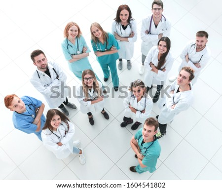 female doctor standing in front of her applauding colleagues #1604541802