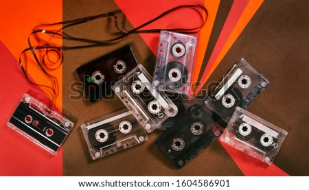 Vintage music cassette tape on retro background. Flat retro lay. 70's, 80's, 90's old school record technology poster. #1604586901