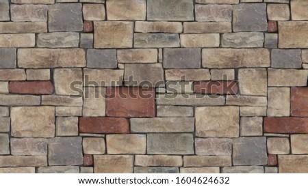 A masonry wall of multicolored stones. Stone wall background #1604624632