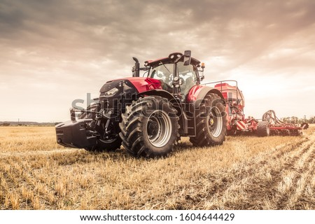 Close photo of modern red tractor with red implement seeding directly into the stubble using GPS for precision farming after a harvest with combine before the Winter.  #1604644429