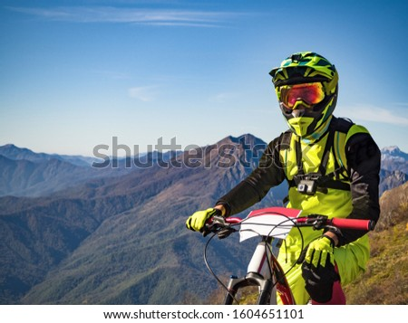 Portrait of downhill rider with full-face helmet and mask on mountain bike #1604651101