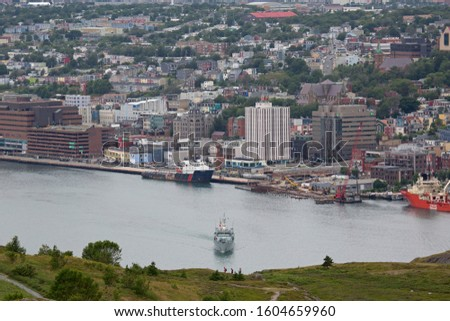 St John's, NL / Canada - 29 July 2019 - Buildings in St John's, Newfoundland and Labrador, Canada. Ships dock in the port. #1604659960