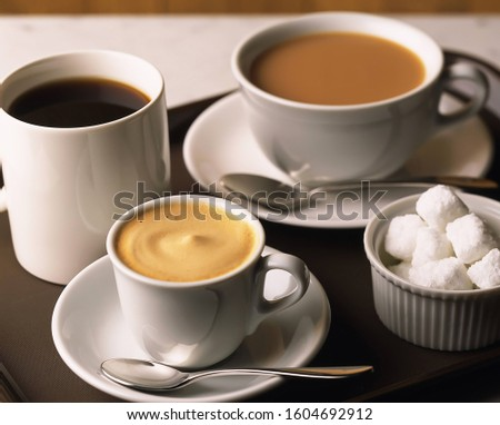 coffee cup with tea cup and spoon with sugar cubes on table on light background, Fresh coffee cup with tea cup and spoon with sugar cubes, Food and drink. #1604692912