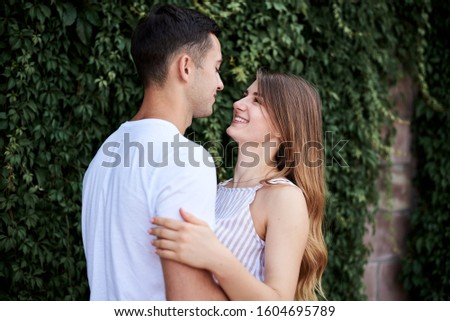 Young couple in love hugging near green bushes trees wall. Pretty blond woman, wearing stripy short overall and brunette man in white t-shirt and blue shorts on romantic date. Romantic relationship #1604695789