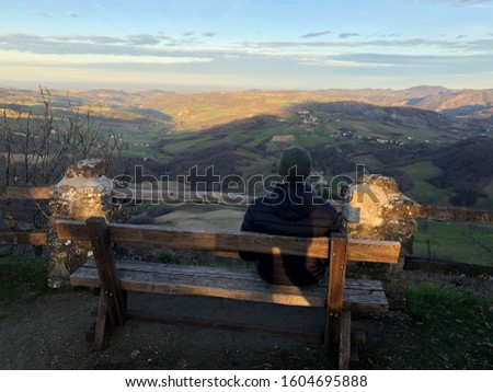 Young man sitting on a bench at sunset in mountains. Lonely man. Lonelines concept. Meditation concept. Happy alone. Traveling alone #1604695888