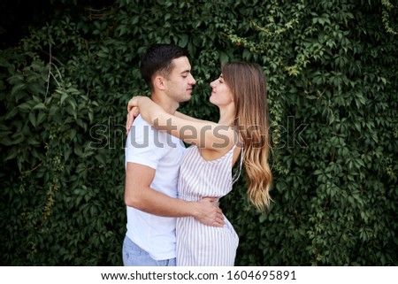 Young couple in love hugging near green bushes trees wall. Pretty blond woman, wearing stripy short overall and brunette man in white t-shirt and blue shorts on romantic date. Romantic relationship #1604695891
