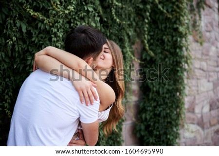 Young couple in love hugging near green bushes trees wall. Pretty blond woman, wearing stripy short overall and brunette man in white t-shirt and blue shorts on romantic date. Romantic relationship #1604695990