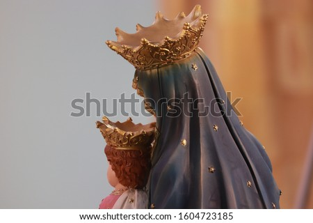 Back pic of Mother Mary holding baby Jesus in her hands they are hiding face because world is full of sin you can see crown on heads of mother Mary Jesus gray and golden and white color