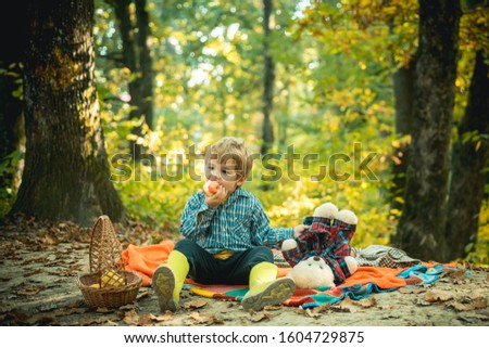Fun walking in the autumnal park. Baby boy holding a teddy bear toy and eating sweet apple. Autumn season concept. Pretty little boy relax on beauty autumn landscape background