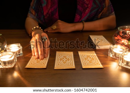 Tarot reader picking tarot cards.Tarot cards face down on table near burning candles and crystal ball.Candlelight in dark.Tarot reader or Fortune teller reading and forecasting concept. #1604742001