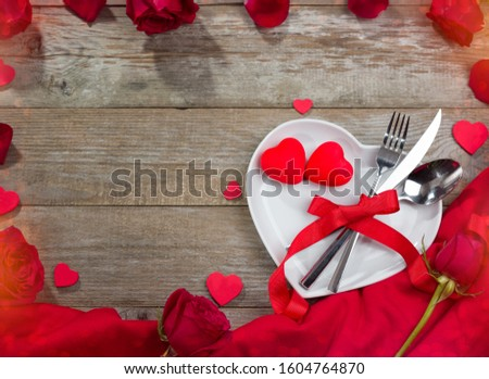 Valentines day dinner concept. Heart shape plate, red tablecloth and roses on table #1604764870