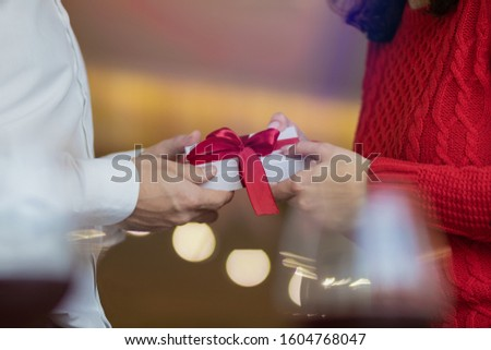 A man passes a white present giftbox with a red ribbon to his girlfriend's hands. Classic look of a couple, red sweater and white shirt. Valentine's day and winter holidays concept. #1604768047
