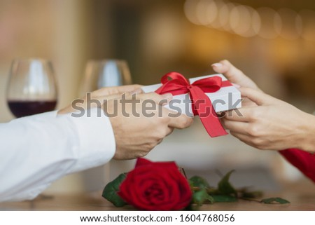 Man passes a white giftbox with a red ribbon to his girlfriend. A young woman takes a present from her boyfriend. Two glasses of wine and a rose on the cafe's table. Valentine's day concept. #1604768056