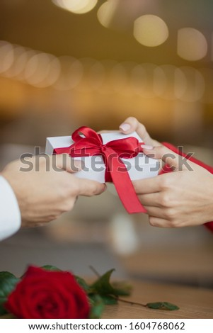 Man passes a white giftbox with a red ribbon to his girlfriend. A young woman takes a present from her boyfriend. Two glasses of wine and a rose on the cafe's table. Valentine's day concept. #1604768062
