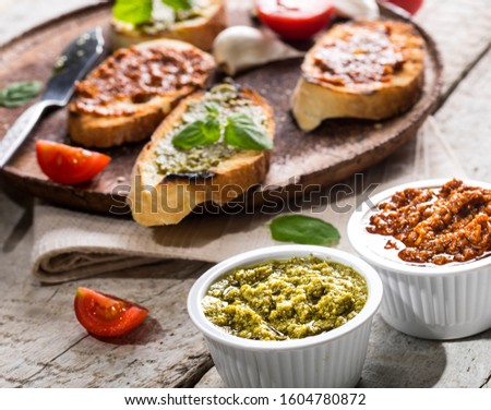 Sliced traditional toast bread with basil pesto and tomato pesto on a cutting board and white wooden table. #1604780872