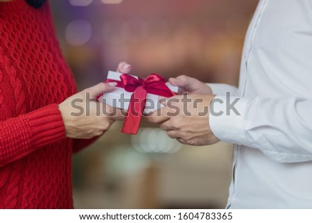 A man passes a white present giftbox with a red ribbon to his girlfriend's hands. Classic look of a couple, red sweater and white shirt. Valentine's day and winter holidays concept. #1604783365