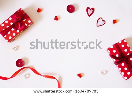 The Background Of Valentine's Day. Gifts with bows, candles, confetti, red satin ribbon, hearts on a light background. The Concept Of Valentine's Day. Flat lay, top view, copy space #1604789983