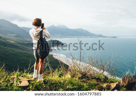 Rear view of a young woman on the top of a mountain, taking a picture with her smartphone of the beautiful landscape on the Asia coast near the sea, seascape, travel to the mountains