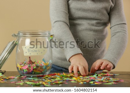Adorable toddler girl playing with a jar full of confetti, hope, wishes and dreams concpet, serie of photos #1604802154