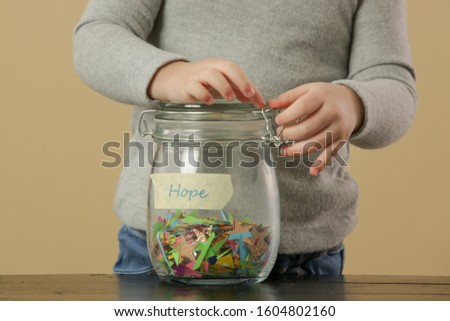 Adorable toddler girl playing with a jar full of confetti, hope, wishes and dreams concpet, serie of photos #1604802160
