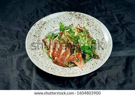 Salad with spinach, lettuce, olive oil, smoked eel in a stylish white ceramic plate on a black background. Healthy and diet food. Seafood salad #1604803900