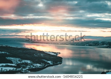 Sunrise, sunset picture in winter, in Scandinavia. Snowie mountains and trees. Travel photography, copy space.