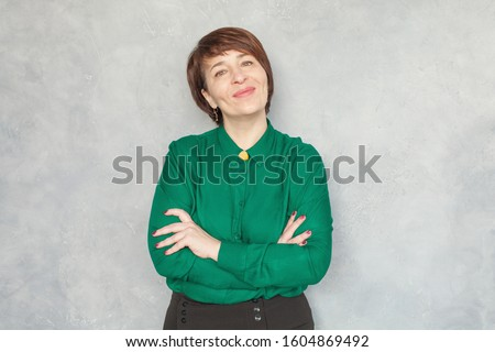 Smiling mature woman wearing green shirt on gray background, portrait #1604869492