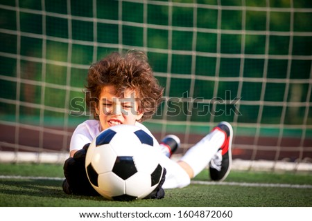 Young soccer goalie attempting to make a save. little soccer goalkeeper with gloves. Kids - soccer champion. Boy goalkeeper in football sportswear on stadium with ball. Sport concept. Selective focus.