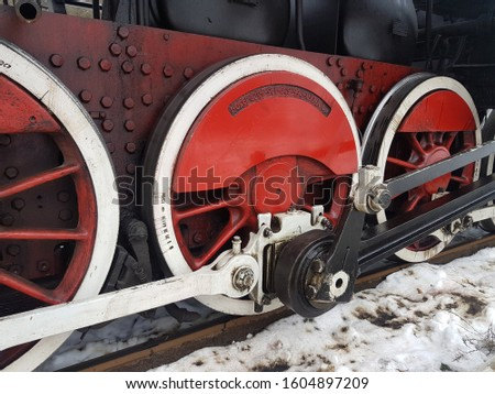 Red and white metal wheels of a retro train. Three wheels connected by rungs.  The lower part of the railway carriage. Black and red aesthetics. #1604897209