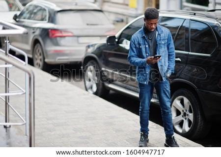 African man wear on jeans jacket posed outdoor, standing against black car with mobile phone at hand. #1604947717