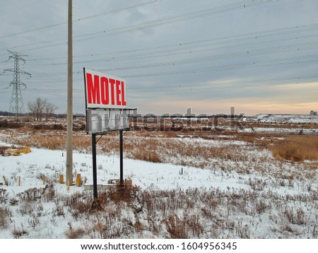Motel is torn down and all that remains is a weathered sign #1604956345