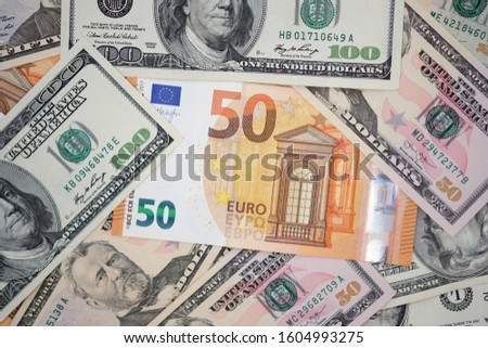 Fifty euro bill and dollars banknote around. Two different currencies. Banknotes background. #1604993275