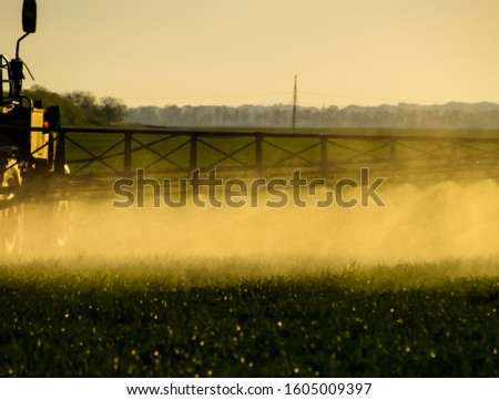Jets of liquid fertilizer from the tractor sprayer. Tractor with the help of a sprayer sprays liquid fertilizers on young wheat in the field. The use of finely dispersed spray chemicals. #1605009397