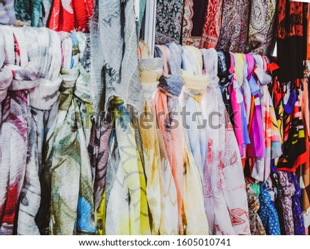 Indian fabrics hanging on the counter. Trade in fabrics from india. Fabric with patterns and patterns. #1605010741