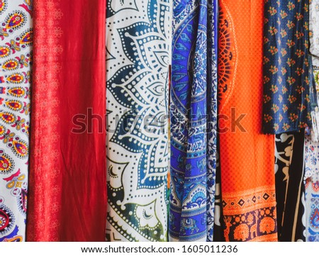 Indian fabrics hanging on the counter. Trade in fabrics from india. Fabric with patterns and patterns. #1605011236