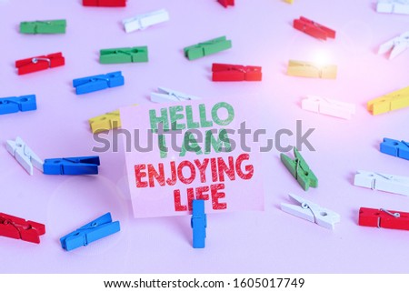 Text sign showing Hello I Am Enjoying Life. Conceptual photo Happy relaxed lifestyle Enjoy simple things Colored clothespin papers empty reminder pink floor background office pin. #1605017749
