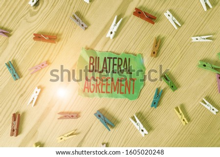 Conceptual hand writing showing Bilateral Agreement. Business photo showcasing Legal obligations to nonbinding agreements of principle Colored crumpled papers wooden floor background clothespin. #1605020248