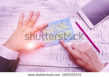 Conceptual hand writing showing Bilateral Agreement. Business photo text Legal obligations to nonbinding agreements of principle Hand hold note paper near writing equipment and smartphone. #1605020335