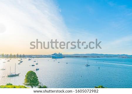 cruiseship leaving Tauranga Harbour at sunrise with bright light of sun illuminating from side.
