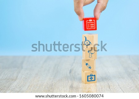 Close-up hand choose a red wooden toy blocks with insurance policy icon for health insurance concepts. #1605080074