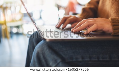 Closeup image of a woman working and typing on laptop computer #1605279856