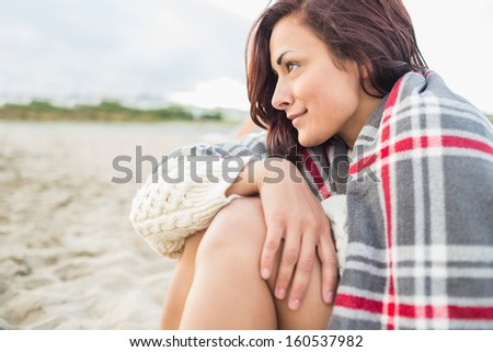 Side view of a young woman covered with blanket at the beach #160537982
