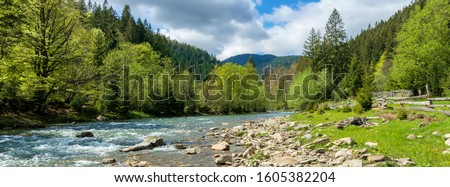 river in mountains. wonderful springtime scenery of carpathian countryside. blue green water among forest and rocky shore. wooden fence on the river bank. sunny day with clouds on the sky #1605382204