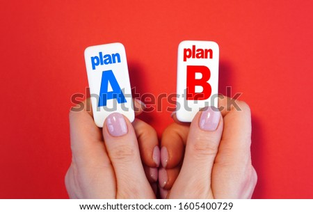 Planning. Plan A and plan B concept with blocks with text in a hands. #1605400729