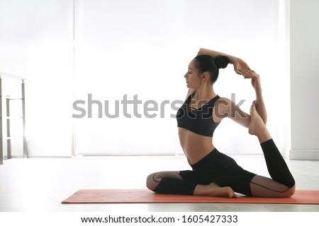 Woman practicing mermaid asana in yoga studio. Eka pada rajakapotasana pose #1605427333