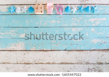 Summer time vacation concept. Beach Accessories model wooden house,chair,shoe with sea shells and starfish on Blue vintage wooden background. flat lay picture