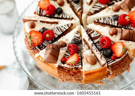 Chocolate cheesecake black and white with strawberries, raspberries, blueberries, on a glass plate. Picture for a menu or confectionery catalog